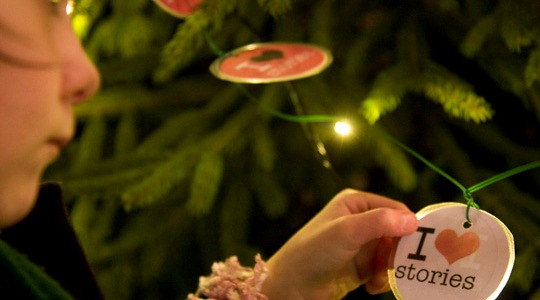 A photo of a child holding a Christmas decoration saying I love stories