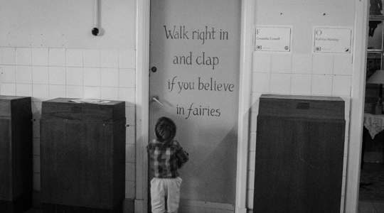 Image: Small boy stands by a door, which reads: 'Walk right in and clap if you believe in fairies.'