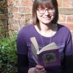 A photo of Beverley Moore holding the book The Diddakoi by Rumer Godden