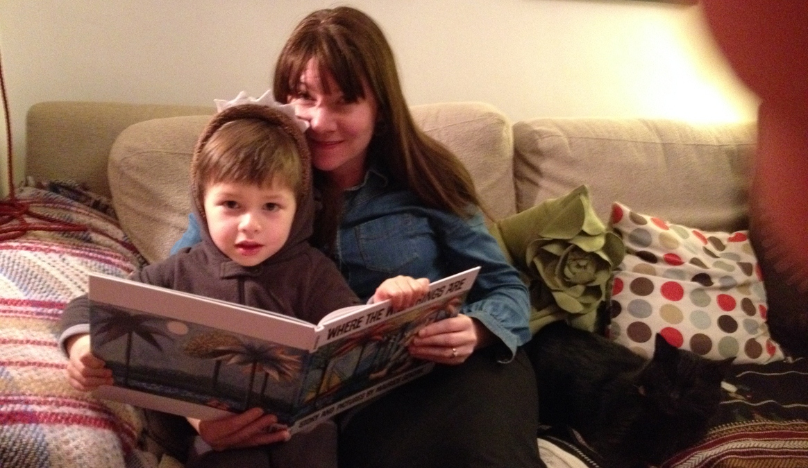 A photo of mother and child reading a book Where The Wild Things Are