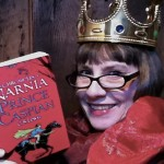 A photo of Faye Sharp dressed as a Prince holding the book Prince Caspian by C.S. Lewis