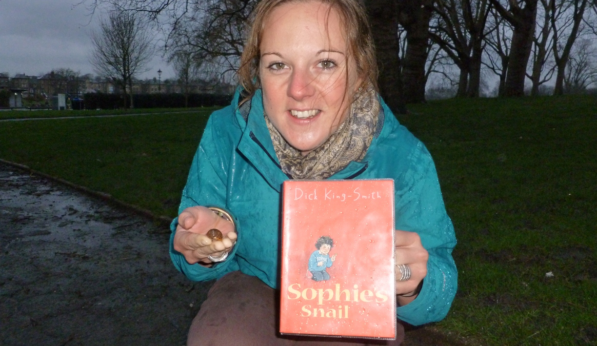 A photo of Jo Wigley holding a snail in her right hand and the book Sophie's snail in her left hand