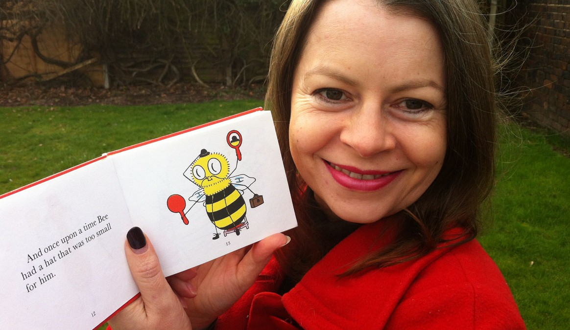 A photo of Justina Hart with a picture book about a bee