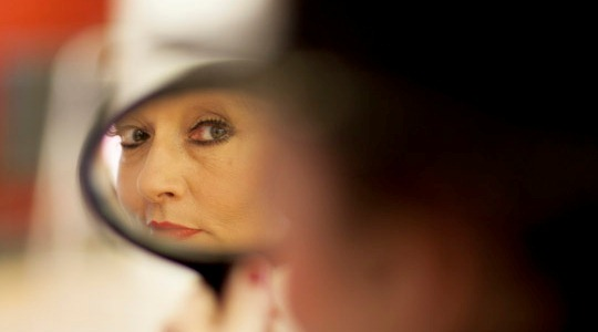 A photo of Katrice Horsley looking in a mirror