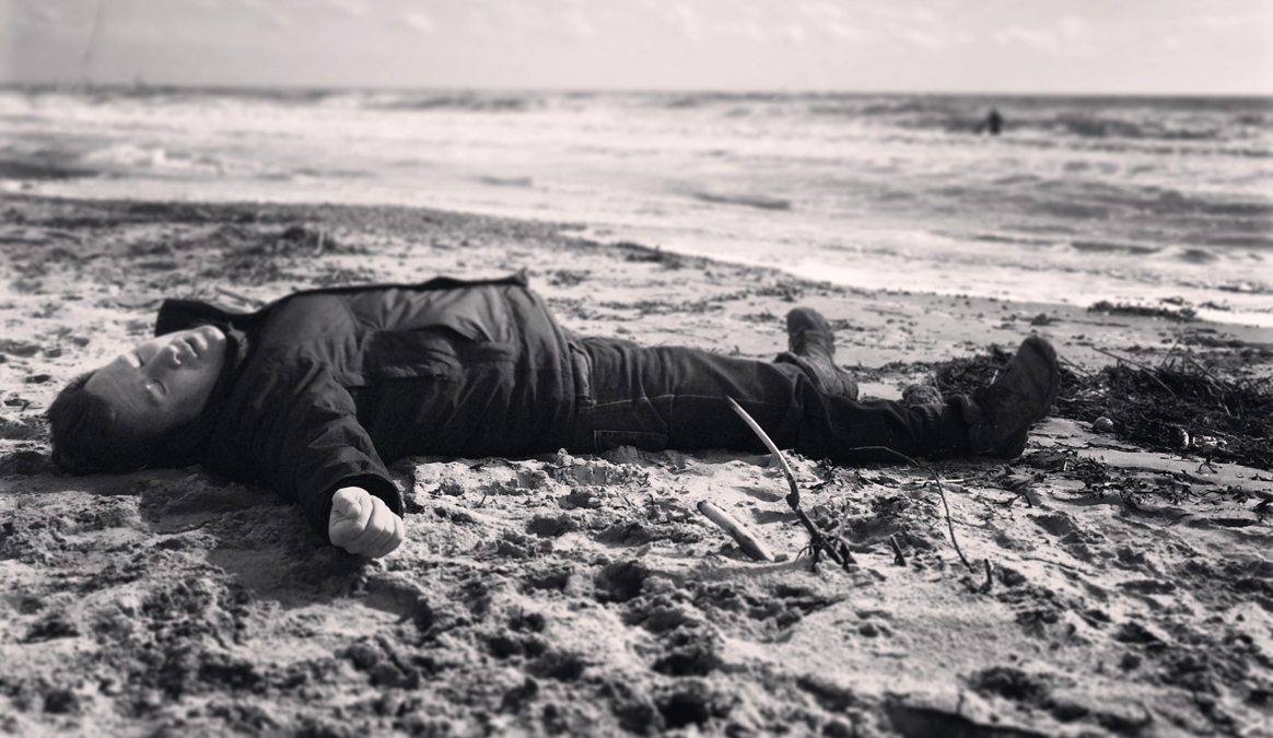 A photo of Neil Baker lying on the sand at the beach