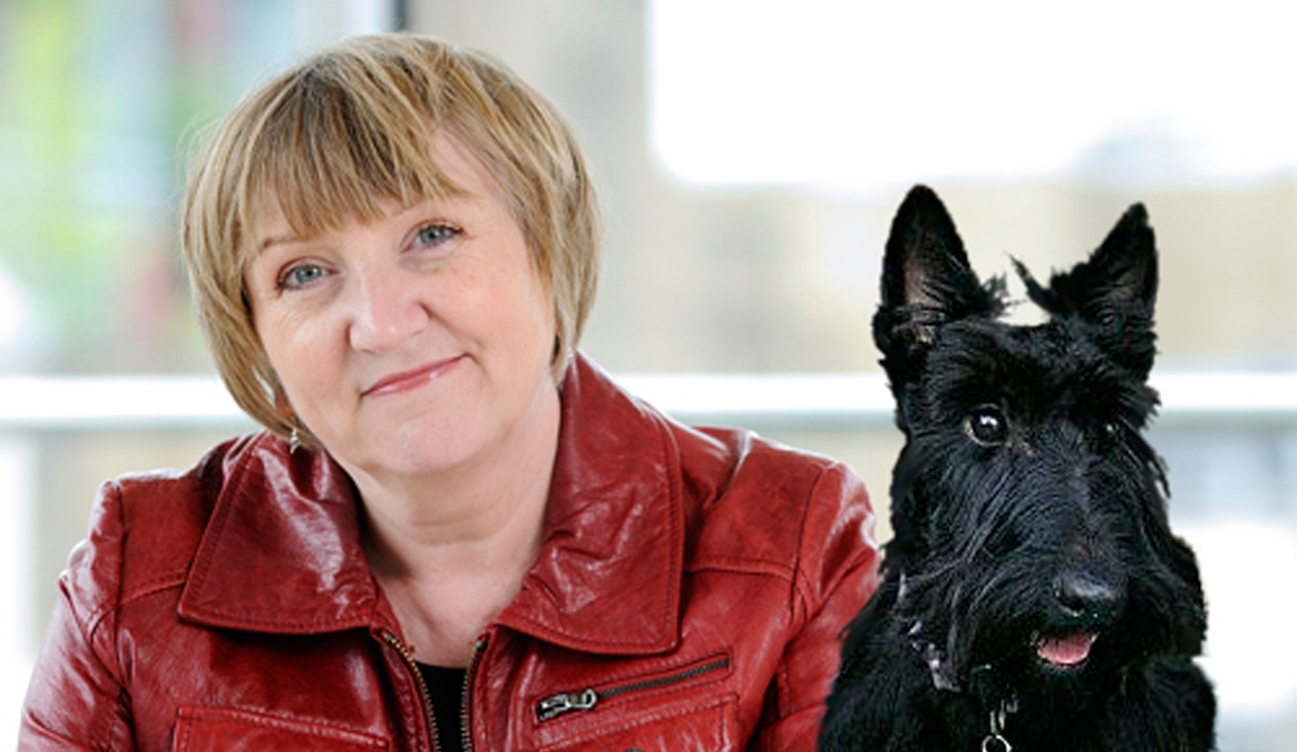 A photo of Phillippa Cowley-Thwaites with a black dog