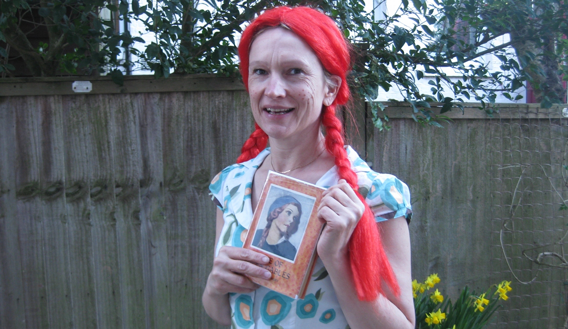 A photo of Rebecca Dowman in a red wig holding the book Anne of Green Gables