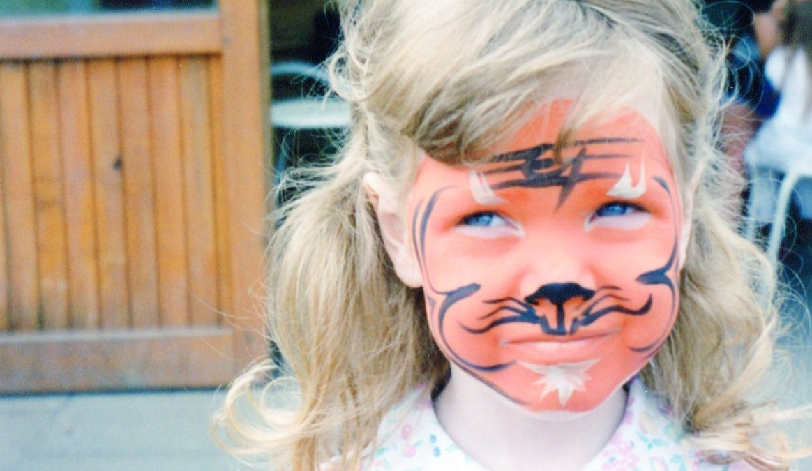 A photo of a girl with her face painted as a tiger