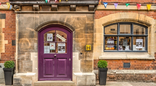 Image: the purple front door of The Story Museum's shop and café
