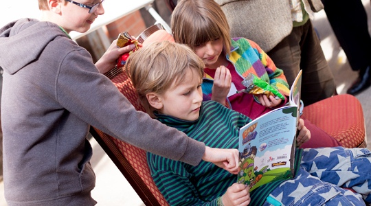 Image: three children reading a comic book.
